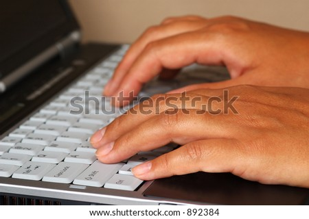 Woman is typing on a notebook. Closeup shot of hands. - stock photo