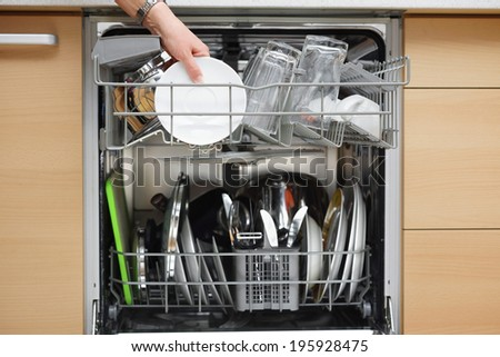 woman is using a dishwasher in a modern kitchen - stock photo