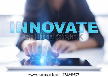 "Woman is using tablet pc, pressing on virtual screen and select ""Innovate""."