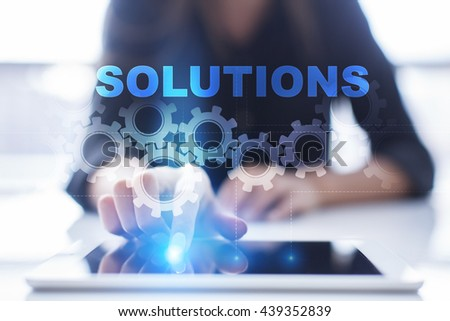 "Woman is using tablet pc, pressing on virtual screen and select ""solutions"".  - stock photo"