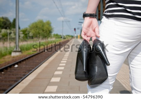 Woman is waiting with her shoes in her hand.