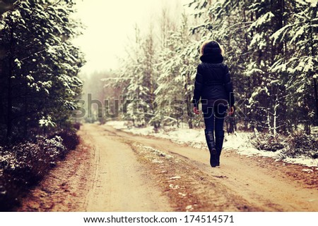 Woman is walking through forest in wintertime. Alone woman is going in cold day. - stock photo