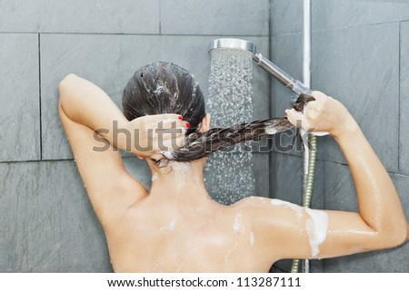 Woman is washing her brown hair - stock photo