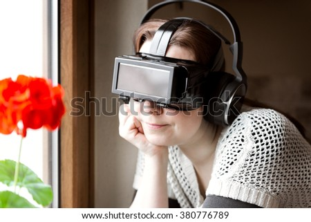 woman is wearing vr glasses, leaning at a window