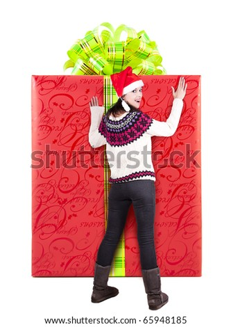 Woman is wondering and standing near extra large red gift - stock photo
