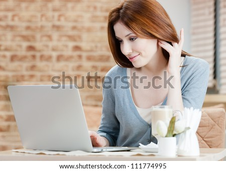 Woman is working on the laptop at the internet cafe - stock photo