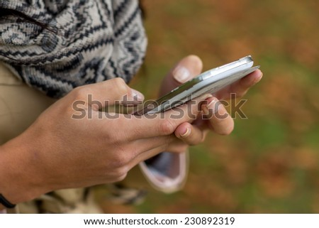 Woman is writing a sms on her mobile phone - stock photo