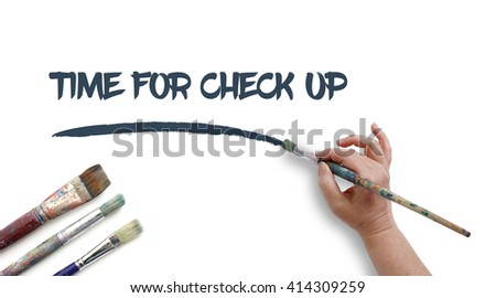 Woman is writing TIME FOR CHECK UP with paintbrush.