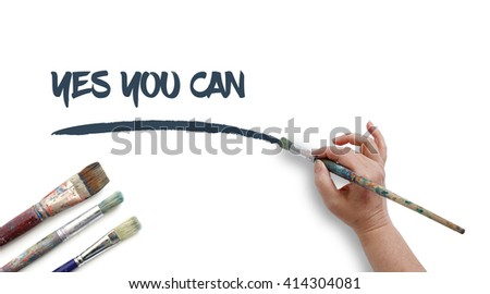 Woman is writing YES YOU CAN with paintbrush.