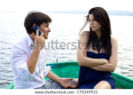 Woman jealous about boyfriend on the phone talking and smiling - stock photo
