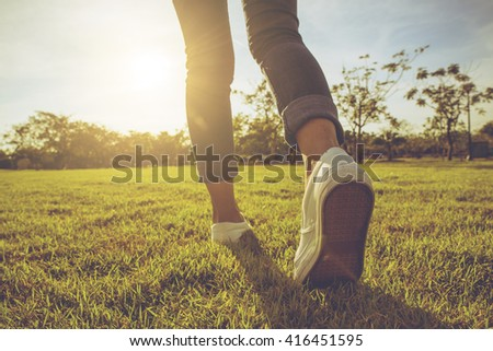 Woman jeans and sneaker shoes on the grass sunset - stock photo