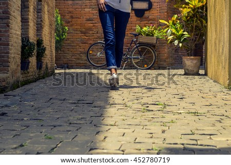 Woman jeans and sneaker shoes walking in vintage city on rocky Road