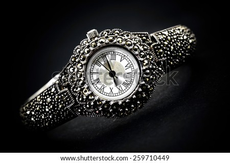 woman jewelery wristwatch on black background - stock photo