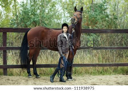 Woman jockey is riding the horse outdoor - stock photo