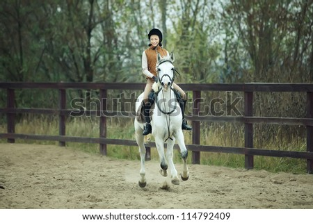 Woman jockey is riding the horse outdoor - stock photo