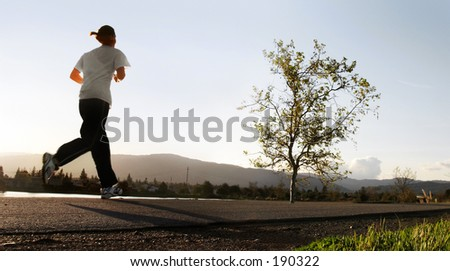 woman jogging along a river in the morning - stock photo