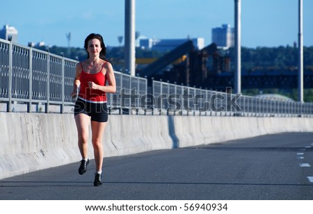 Woman jogging at the highway, front view - stock photo