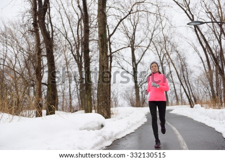 Woman jogging in snowy city park - winter fitness. Female athlete exercising outside in cold weather on forest path wearing activewear. Windbreaker pink jacket, warm tights, running shoes. - stock photo