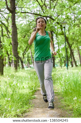 Woman jogging in the park - stock photo