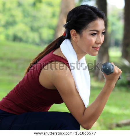 woman jogging on running trail with hand weights. - stock photo