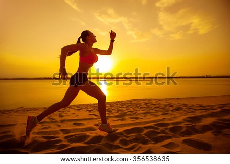 Woman jogging on the beach at sunset .