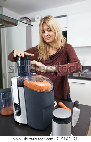 Woman juicing carrots at kitchen counter