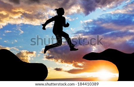 Woman jump over canyon at a sunset