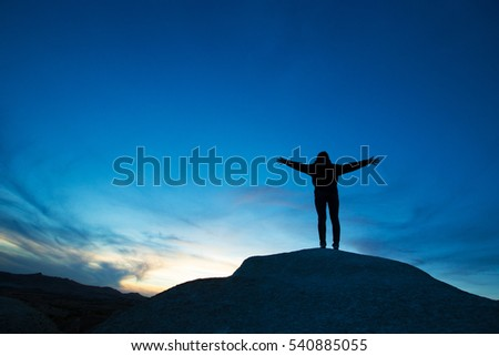 woman jumping against sunset with blue sky