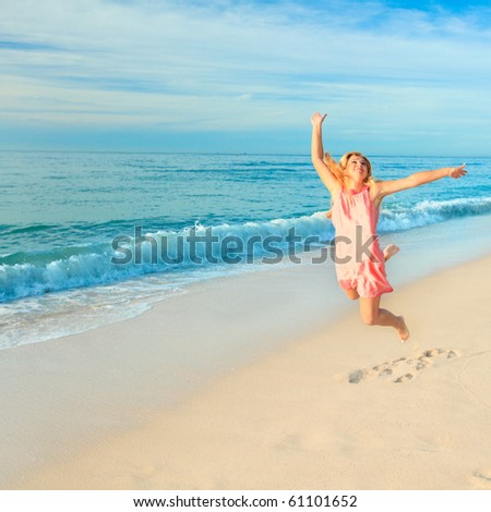 Woman jumping at a white sand beach - stock photo