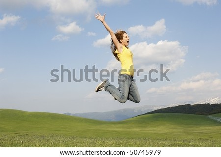 Woman jumping for joy in mountain meadow, side view - stock photo
