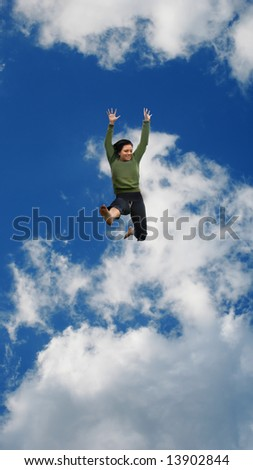 Woman jumping high into the blue sky with puffy clouds.