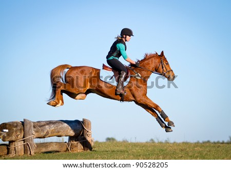Woman jumping horse over log on cross country course - stock photo
