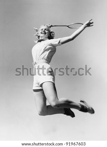 Woman jumping into the air with a tennis racket in her hand - stock photo