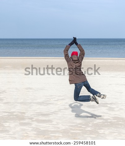 Woman jumping on beach, winter active lifestyle concept, space for text. - stock photo