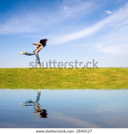 Woman jumping on green field, with water reflection. - stock photo
