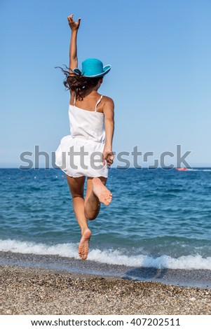 Woman jumping on the beach. - stock photo