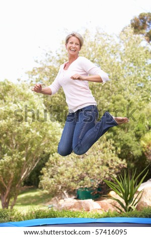 Woman Jumping On Trampoline In Garden - stock photo