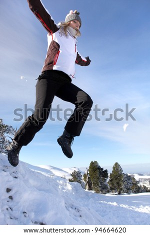 Woman jumping onto a pile of snow - stock photo