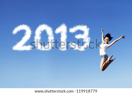 Woman jumping under clear blue sky with 2013 clouds next to her - stock photo