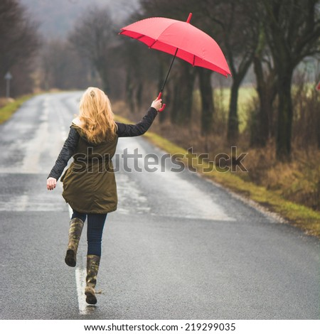 Woman jumping with umbrella - stock photo