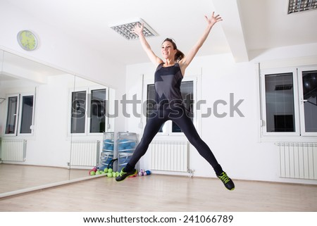 woman jumps in empty gym - stock photo