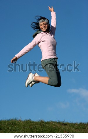 woman jumps outdoors in a sunny day against a very blue sky