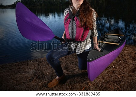 woman kayaker and a purple kayak at lake in the fall with a plaid shirt and jean - stock photo