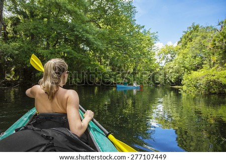 Woman kayaker paddling down a beautiful jungle river with two people in a canoe on a gorgeous day. Lots of copy space and view from behind - stock photo