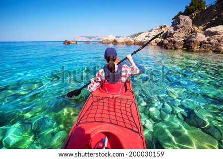 Woman kayaking at sea along the rocky shore of the island. Traveling by kayak. - stock photo