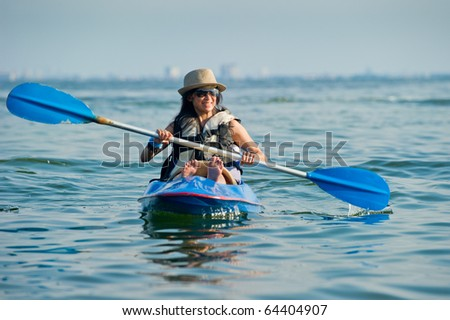woman kayaking in a tropical sea - stock photo