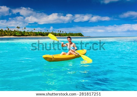 Woman Kayaking in the Ocean on Vacation in tropical Fiji island - stock photo