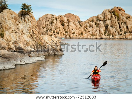 Woman Kayaking on Lake Surrounded by Boulders - stock photo