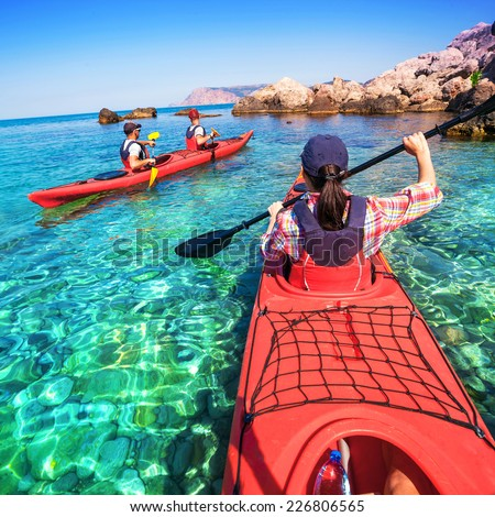 Woman kayaking on the sea with two young men. Canoeing on the islands. - stock photo