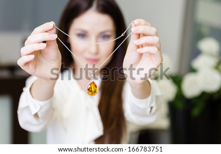 Woman keeping necklace with yellow sapphire at jeweler's shop. Concept of wealth and luxurious life - stock photo